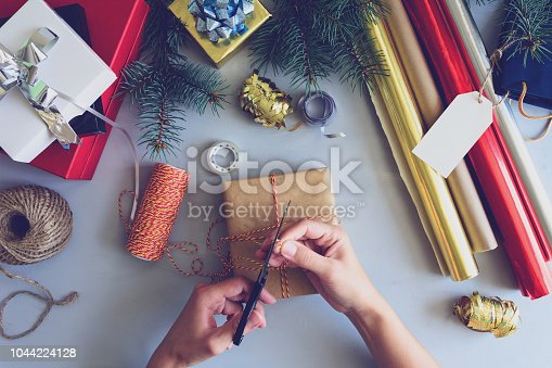 istock Woman's hands decorate present box on gray wooden background. New Year and Christmas decorations concept. Toned 1044224128