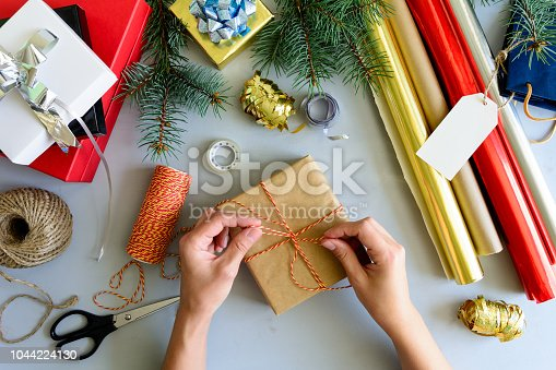 istock Woman's hands decorate present box on gray wooden background. New Year and Christmas decorations concept. 1044224130