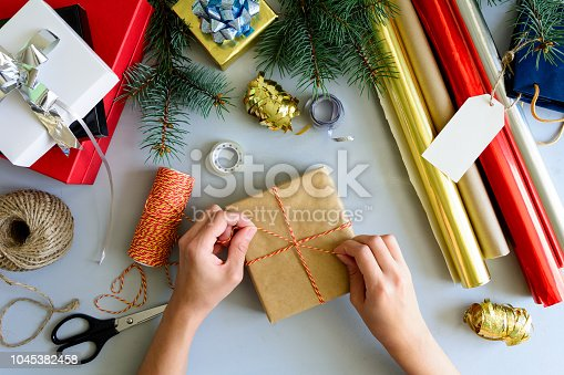 istock Woman's hands decorate present box on gray wooden background. New Year and Christmas decorations concept. 1045382458