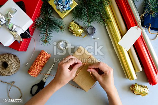 istock Woman's hands decorate present box on gray wooden background. New Year and Christmas decorations concept. 1045382772