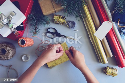 istock Woman's hands decorate present box on gray wooden background. New Year and Christmas decorations concept. Toned 1048799894