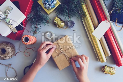 istock Woman's hands decorate present box on gray wooden background. New Year and Christmas decorations concept. Toned 1048799970