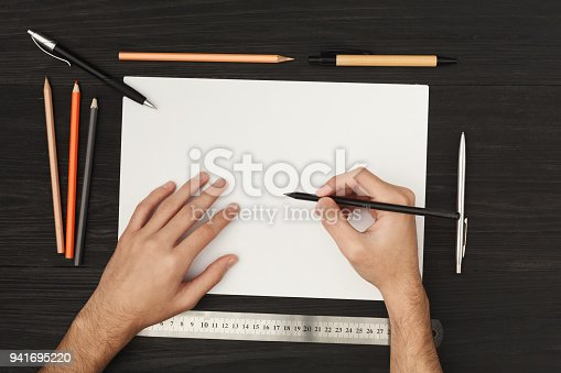 949860388istockphoto Woman's hands drawing on blank paper, top view 941695220