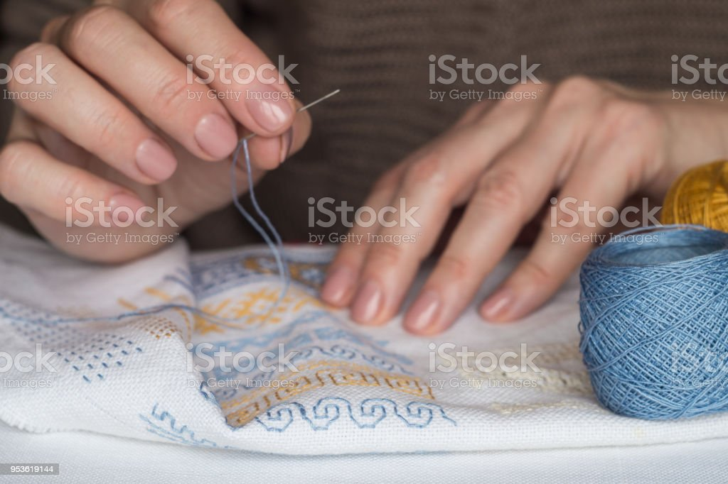 Woman's hands embroider ornaments stock photo