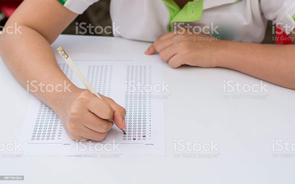 woman's hands filling in standardized test form stock photo