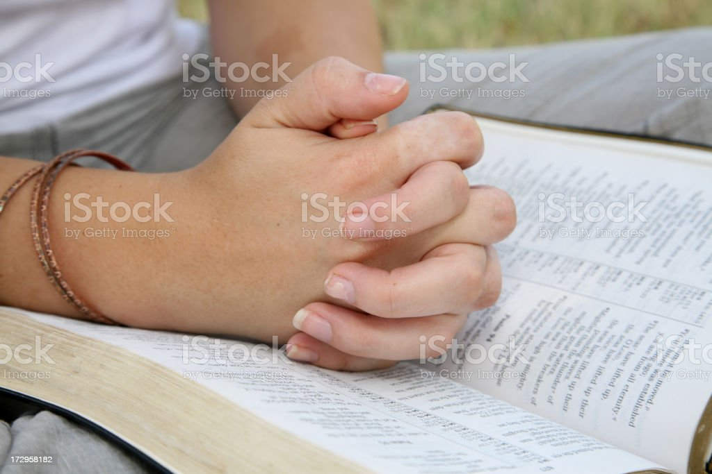 Woman's Hands Folded Together Near A Bible royalty-free stock photo