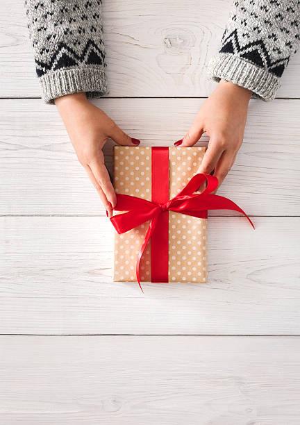 woman's hands give christmas gift in present box - bastelkarton stock-fotos und bilder