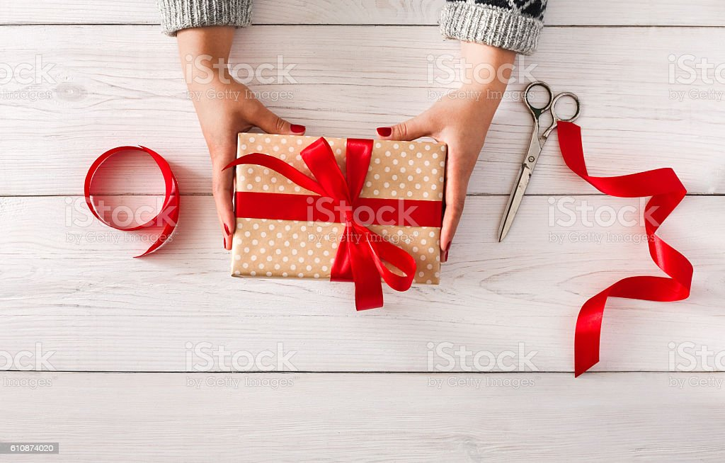 Woman's hands give christmas gift in present box stock photo