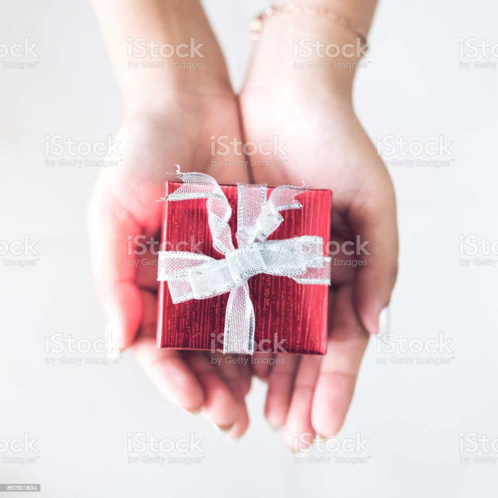 Woman\'s hands give present give wrapped christmas or other holiday...