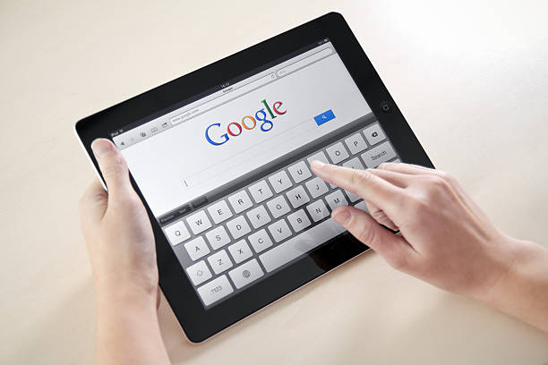 """Woman's hands Googling on electronic device """"Kiev, Ukraine - December 03, 2011: Woman hands holding and touching on Apple iPad2 with Google search web page on a screen. This second generation Apple iPad2 is designed and development by Apple inc. and launched in march 2011."""" google stock pictures, royalty-free photos & images"""