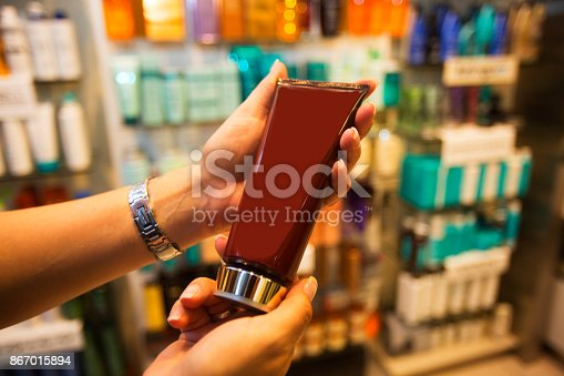 455111881istockphoto Womans hands hold a brown health care tube in a cosmetic store aisle while shopping 867015894