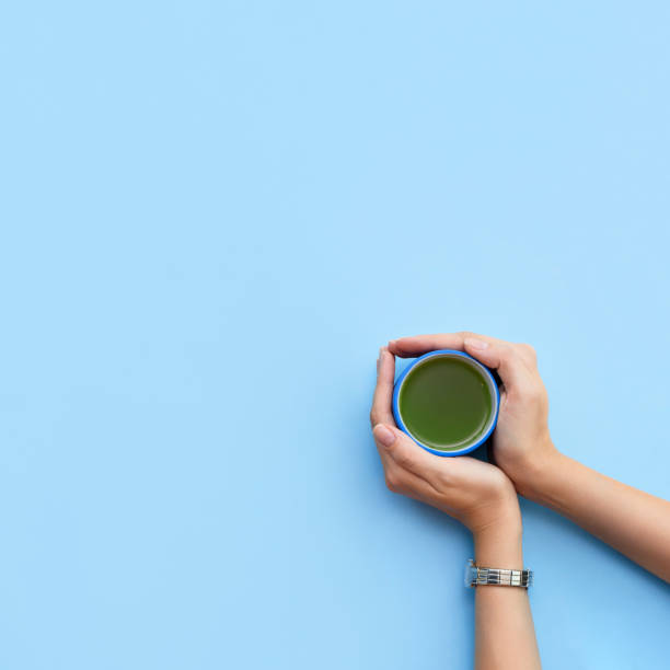 Woman's hands hold a cup of matcha tea on a blue background. Top view. Take away. Woman's hands hold a cup of matcha tea on a blue background. Top view. Take away. greentea stock pictures, royalty-free photos & images