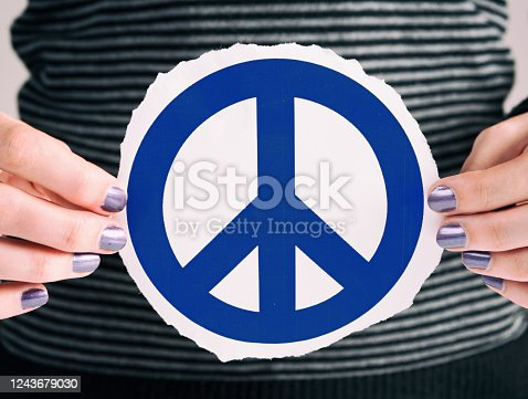 Close-up of woman holding a peace sign.