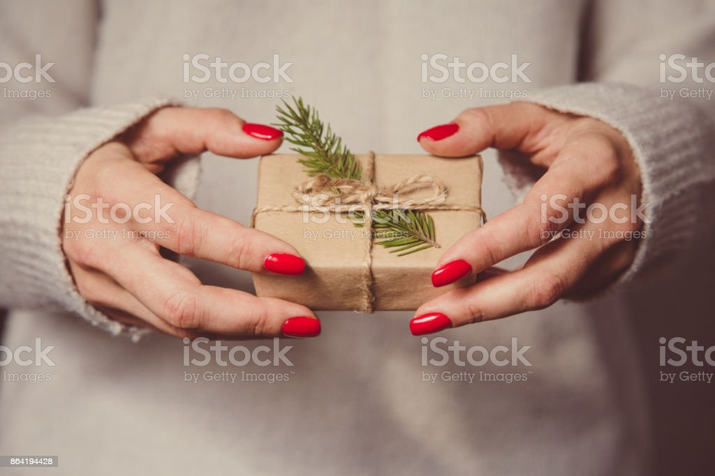 Woman's hands hold christmas or new year decorated gift box. Toned picture royalty-free stock photo