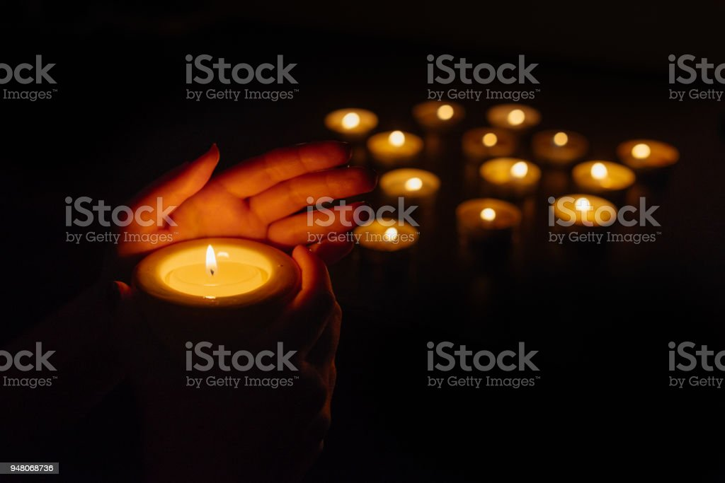 Woman's hands holding a burning candle. Abstract candles background. Many candle flames glowing on dark background. Close-up. Woman's hands holding a burning candle. Abstract candles background. Many candle flames glowing on dark background. Close-up. Black Color Stock Photo