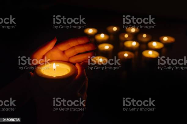 Womans Hands Holding A Burning Candle Abstract Candles Background Many Candle Flames Glowing On Dark Background Closeup Stock Photo - Download Image Now