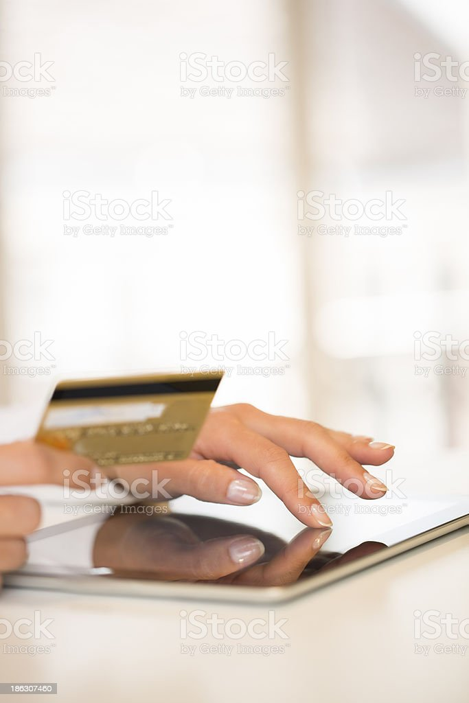 Woman's hands holding a credit card and using tablet pc royalty-free stock photo
