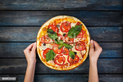 istock Woman's hands holding a perfect pizza margarita with tomato slices, olives and basil leaves. Top view 868803430