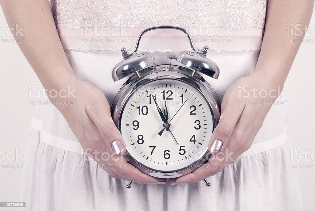 A woman's hands holding a silver alarm clock stock photo