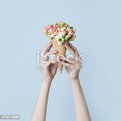 680461500 istock photo Woman's hands holding a waffle cone with spring flowers bouquet on the blue background. Flat lay, top view. Mothers day, anniversary, greetings. 979579586