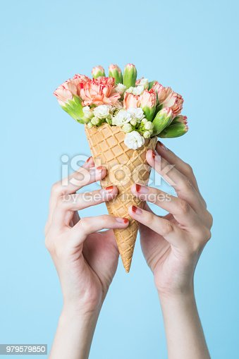 680461500 istock photo Woman's hands holding a waffle cone with spring flowers bouquet on the blue background. Flat lay, top view. Mothers day, anniversary, greetings. 979579850