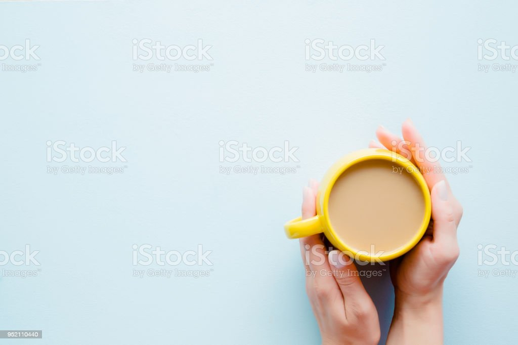 Woman\'s hands holding a yellow mug of coffee with milk on light...