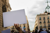woman's hands in the foreground holding a blank banner to put the message you want during a demonstration in the streets of an European city