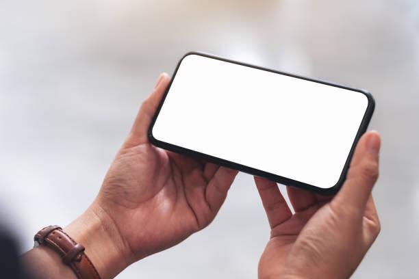 Frauenhände halten schwarzes Handy mit leerem Desktop-Bildschirm – Foto