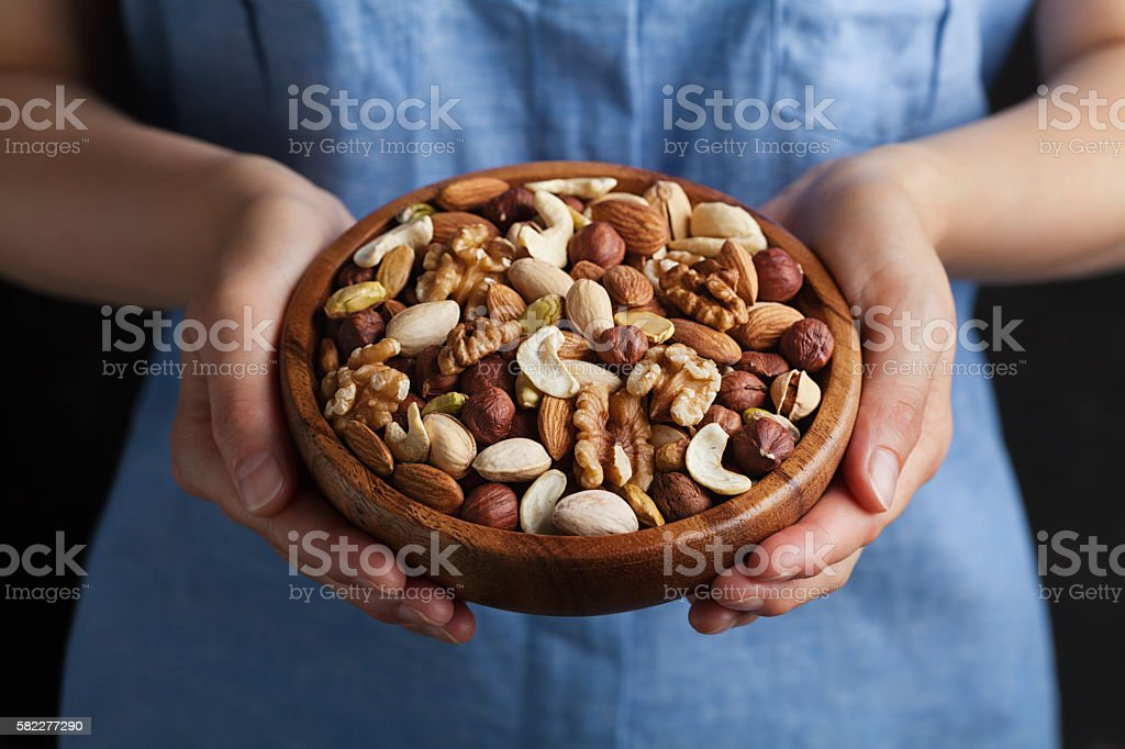 Womans hands holding bowl with nuts. Walnut, pistachios, almonds, hazelnuts – Foto