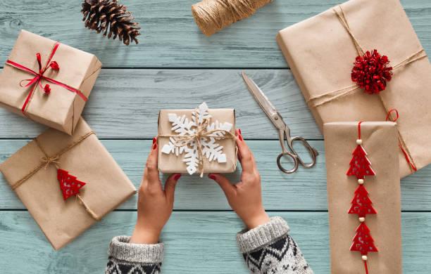 frauenhand weihnachtsferien präsent halten dekoriert mit schneeflocke - bastelkarton stock-fotos und bilder