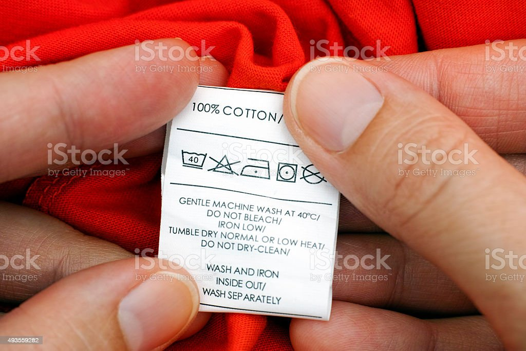 Woman's hands holding clothes label stock photo
