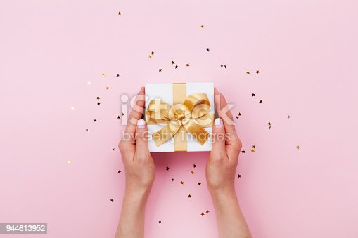 istock Womans hands holding gift or present box decorated confetti on pink pastel table top view. Birthday or wedding template or mockup. 944613952