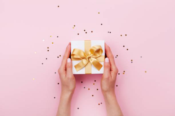 kobiety ręce gospodarstwa prezent lub obecne pudełko urządzone konfetti na różowy pastelowy widok na stole. szablon urodzinowy lub ślubny lub makieta. - gift zdjęcia i obrazy z banku zdjęć