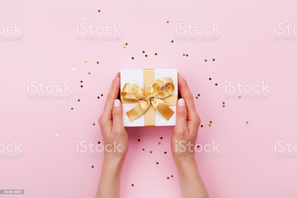 Womans hands holding gift or present box decorated confetti on pink pastel table top view. Birthday or wedding template or mockup. stock photo