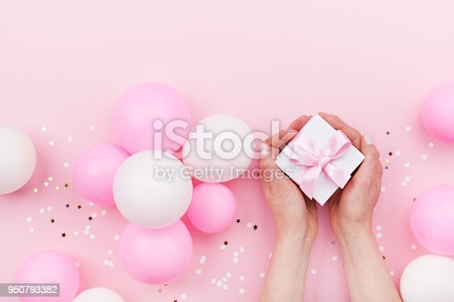 950793576 istock photo Womans hands holding gift or present box on pink pastel table decorated balloons and confetti. Flat lay. 950793382