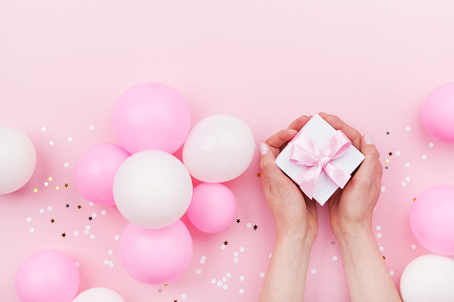 627933752 istock photo Womans hands holding gift or present box on pink pastel table decorated balloons and confetti. Flat lay. 950793382