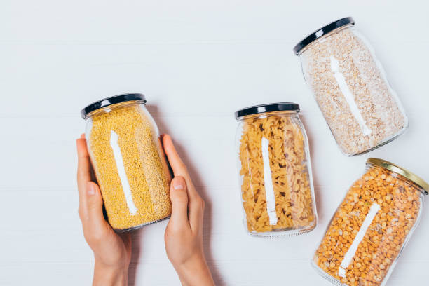 Woman's hands holding glass jar of millet stock photo