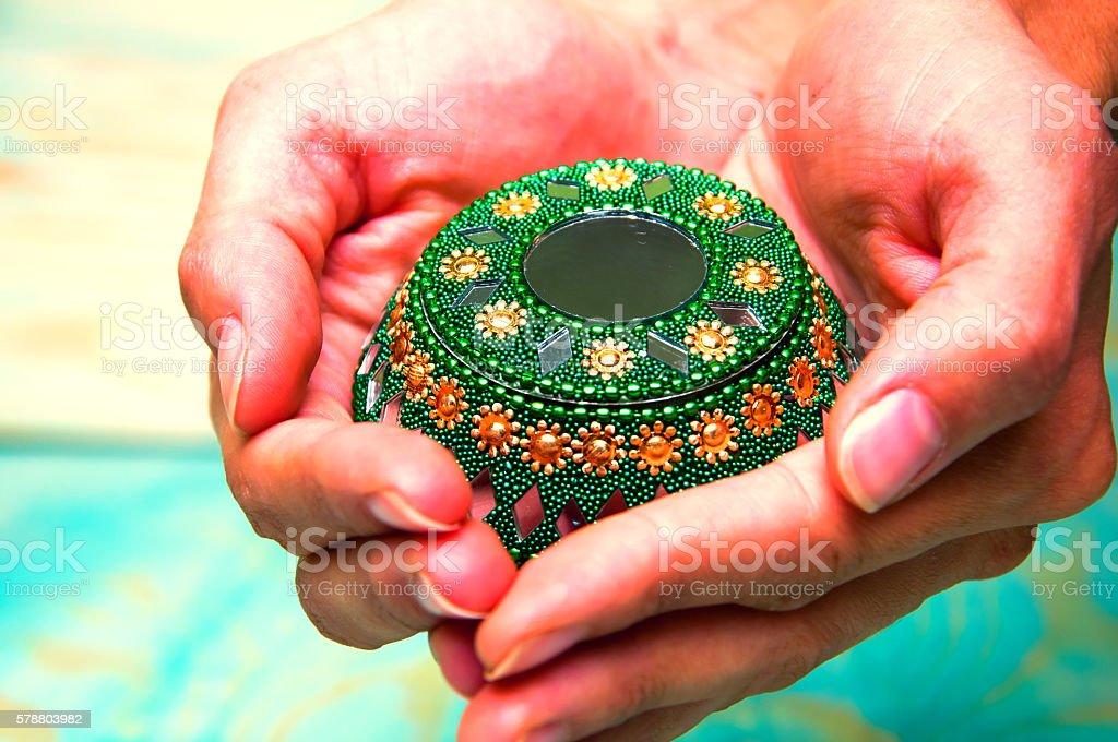 Woman's hands holding green oriental casket stock photo