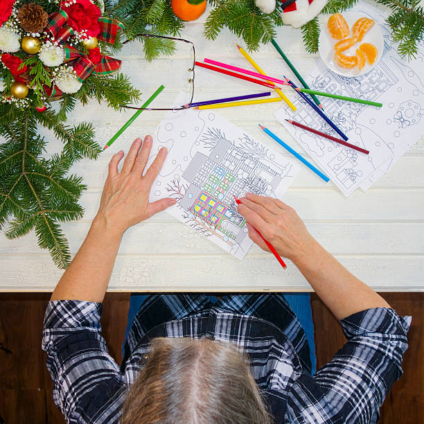 woman's hands holding green pencil crayon coloring a design page - ausmalbilder weihnachtsmann stock-fotos und bilder