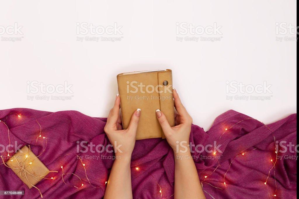 Mãos de mulher segurando um caderno em couro tampa sobre a mesa branca - foto de acervo