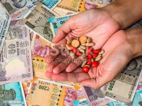 istock Woman's hands holding pills over 10, 20, 50, 100, 200, 500 and 2000 Indian rupees 1073829764