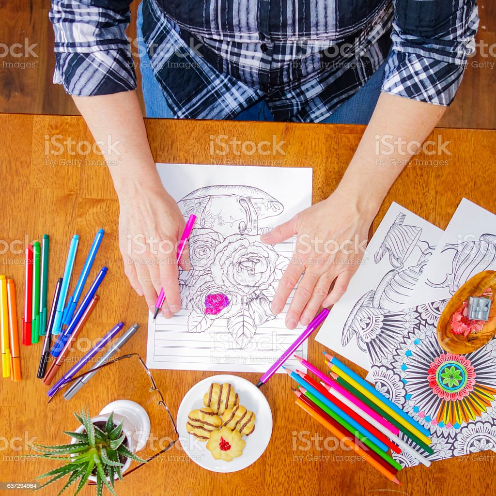 Woman's Hands Holding  Pink Marker with a Flower coloring page stock photo
