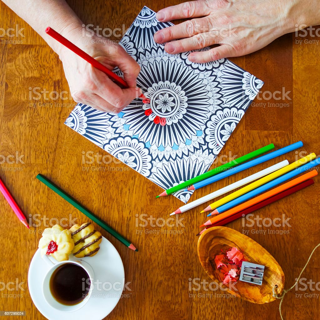 Woman's Hands Holding Red Pencil Crayon Coloring a Design Page stock photo