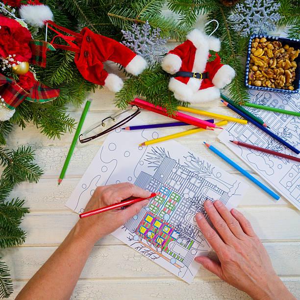 woman's hands holding red pencil crayon coloring a design page - ausmalbilder weihnachtsmann stock-fotos und bilder