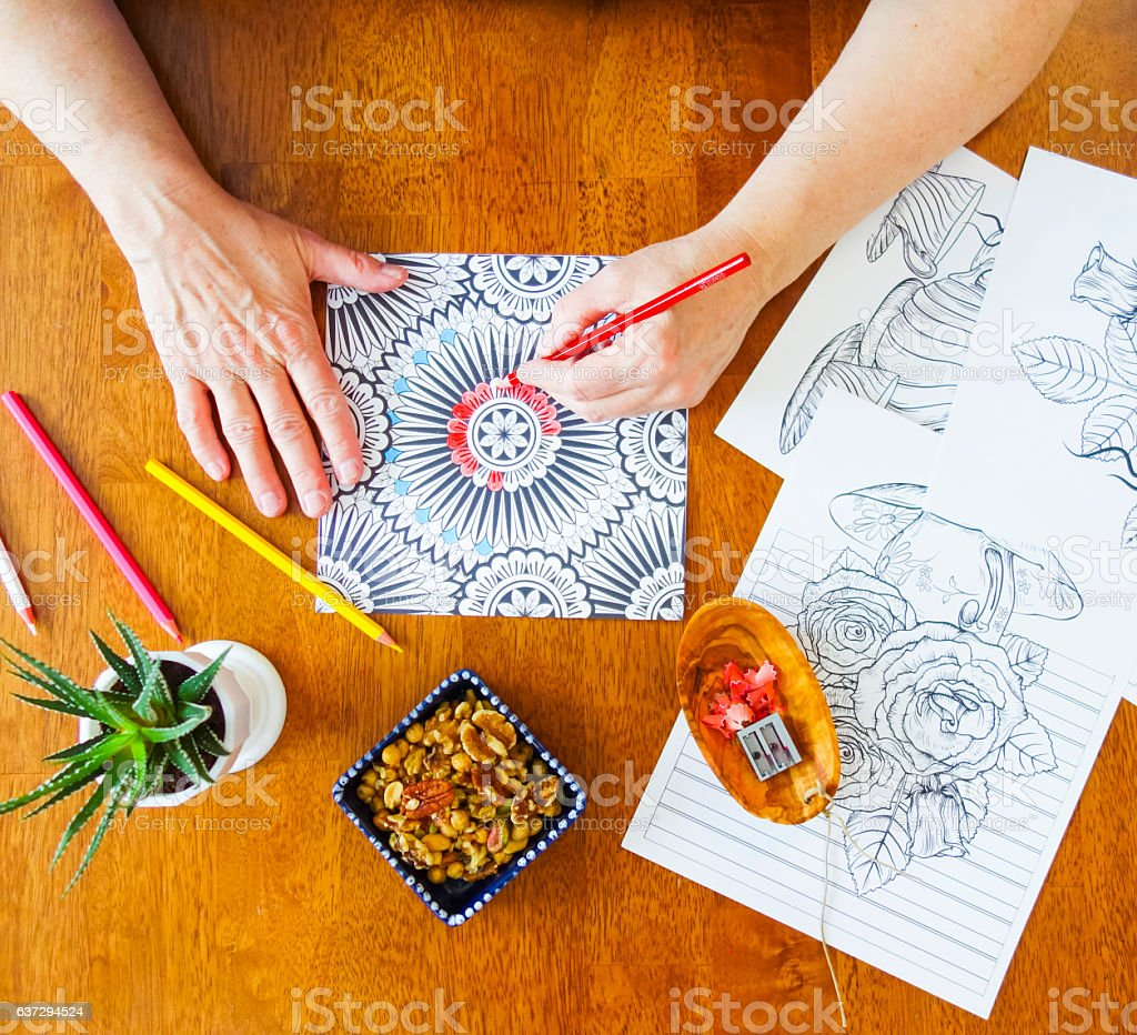 Woman's Hands Holding Red Pencil Crayon in Left Hand Coloring stock photo