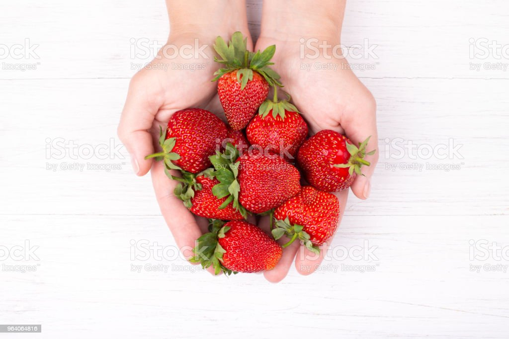Womans hands holding srawberries. - Royalty-free Adult Stock Photo