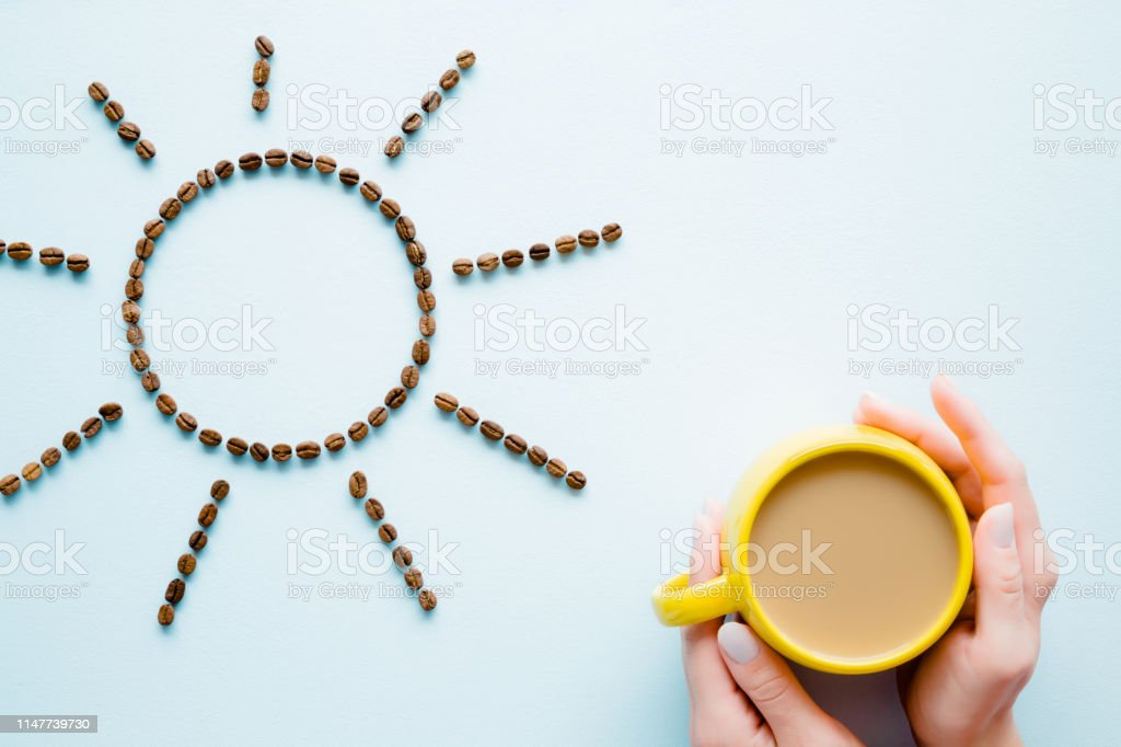 Woman\'s hands holding yellow mug of coffee with milk on light pastel...