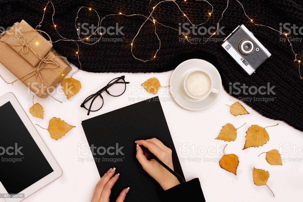 As mãos de mulher com uma camisola de malha preta, segurando a caneta perto do papel em branco, Ver os de cima - foto de acervo