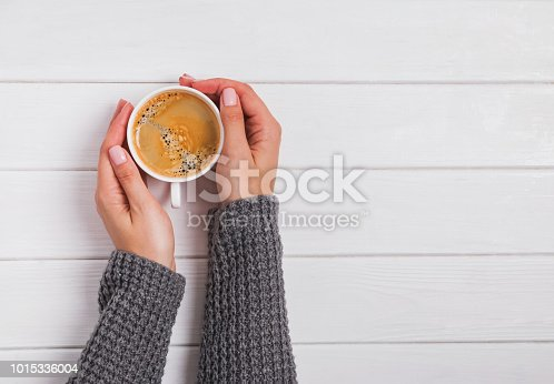 istock Woman's hands in knitted sweater holding a cup of coffee on the white wooden background 1015336004