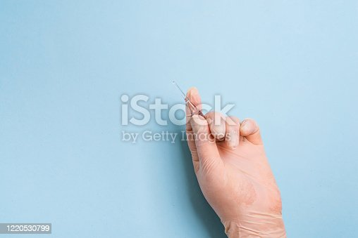 istock Woman's hands in the medical gloves holds vaccine ampoule on a light blue background. 1220530799
